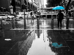 Double Blue (HaIogen) Tags: street people wet rain umbrella reflections blackwhite olympus panasonic orchardroad selectivecolouring explored waveletsharpen 14mmf25 omdem5