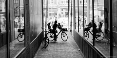 Turning around isn't easy (Johan Konz) Tags: street silhouette bicycle mother children family people amsterdam netherlands windows reflections outdoor blackandwhite monochrome nikon d90