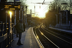 Time Change (Sven Loach) Tags: uk trees england sun cold london clock lines station evening hoodie spring waiting warm time britain candid platform tracks streetphotography passengers wires rails change hackney overground reportage eastlondon tfl hackneycentral