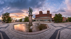 Panorama of Oslo City Hall in the Evening, Oslo, Norway (ansharphoto) Tags: city travel blue sunset vacation sky urban panorama sculpture building tree tower history clock tourism water fountain oslo norway statue skyline architecture modern facade square evening town hall twilight europe european cityscape exterior view outdoor dusk cityhall famous capital landmark illuminated norwegian capitol townhall nordic scandinavia iconic radhuset guildhall scandanavia