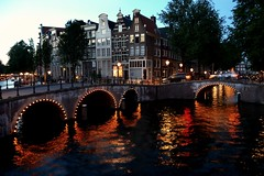 Reflections on the Canal (Clare-White) Tags: amsterdam summer night water canal reflection orange lights bridge buildings windows motion arches tunnels bw city nederlands dutch trees street attraction citybynight glow