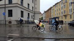 Best-dressed on that rainy day in Munich, Germany (SomePhotosTakenByMe) Tags: city building rain bike bicycle germany munich münchen bayern deutschland bavaria downtown outdoor surfer stadt surfboard gebäude fahrrad regen innenstadt kurios surfbrett outoftheordinary prinzregentenstrase