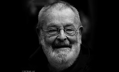 The argument in favor of happiness. (Neil. Moralee) Tags: neilmoralee neilmoraleenikond7100 happy hapiness alive health good joy smile man old mature beard white black bw blackandwhite mono monochrome neil moralee nikon d7100 18300mm face portrait candid glasses bald balding hair receeding blackbackground people close pease tranquility tranquil mood grin cheeky