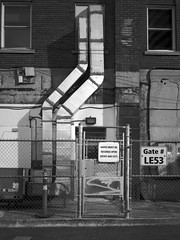 LE53 (geowelch) Tags: toronto urbanfragments blackwhite downtown film 120 mediumformat portra400bw fujigs645s plustekopticfilm7400 building ducting chainlinkfence gate 645