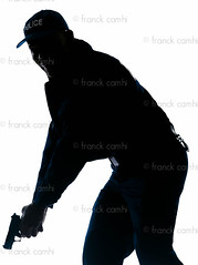 Policeman holding handgun (Franck Camhi) Tags: shadow people man black france male silhouette standing cutout french person one 1 justice holding uniform gun african surveillance authority watch guard police security safety whitebackground crime mature cap weapon cop afroamerican law studioshot handgun protection officer patrol oneperson policeman armed strict oneman vigilance threequarterlength
