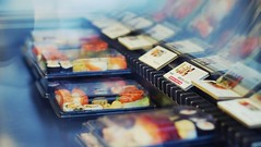 Sushi Boxes (andersdenkend) Tags: city urban fish cinema reflections sushi raw dof bokeh box widescreen depthoffield canned boxes cinematography 169 spiegelung glas mannheim mirroring auslage nikkor50mmf12 cinamtique fujifilmxe1