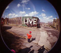 Live (& learn) [Explored #8] (JQ - Who's moving to Ipernity?) Tags: 2 sky film clouds 35mm graffiti iso200 oscar lomo shadows sheffield mosque fisheye hoarding explore contrails 10mm heeley fisheye2 explored fujicoloursuperia
