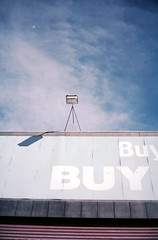 shut up & shop (lonely radio) Tags: sky film clouds 35mm t lights shadows australia melbourne victoria lookup buy f28 sights contaxt3 cremorne pc3121 sonnar carlzeiss auspctagged kodakportra160nc scansf20130525t3p16029