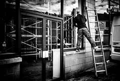 On the edge. (Mister G.C.) Tags: blackandwhite bw image streetshot streetphotography photograph monochrome urban town city man male guy builder workman standing ladder window frombehind zonefocus zonefocusing snapfocus ricoh ricohgr pointshoot mistergc schwarzweiss strassenfotografie scotland britain greatbritain gb british uk unitedkingdom europe
