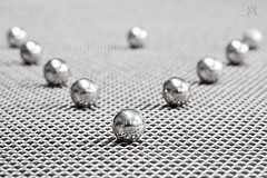 "silver cake decorations on a place mat ""abstract"" (marianna_a.) Tags: p2840958 silver ball bearing cake decoration tiny small macro food sweet"