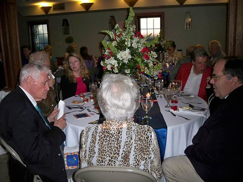 <p>Father Coke McClure, seated with guests at a table featuring one of our hallmark flower arrangements.</p>