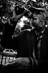 Drink Coca-Cola (stimpsonjake) Tags: nikoncoolpixa 185mm streetphotography bucharest romania city candid blackandwhite bw monochrome cocacola soda oldman drinking hat beard