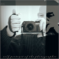 Self portrait with 'M' (fotograf1v2) Tags: selfportrait sp eosmcamera cameragrip picasa3 camera tintedmonochrome greyscale addedtext script photographerwithcamera manipulatedimage graphics computercreativity