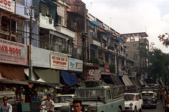 33-522 (ndpa / s. lundeen, archivist) Tags: nick dewolf nickdewolf 33 reel33 color photographbynickdewolf 1970s 1972 fall film 35mm winter 1973 asia vietnam southvietnam vietnamese southvietnamese saigon city citylife street streetlife candid streetphotography people building buildings sign signs store stores shop shops storefront storefronts traffic cars vehicles automobiles parkedcars tarps awnings taxi cab truck