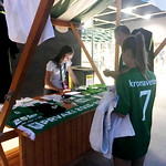 Hostesa NK Olimpija za prodajo nogometnih artiklov na stadionu Stožice.