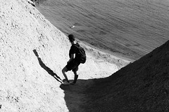 Don't fall (lorenzoviolone) Tags: agfascala200 bw backpack blackwhite blackandwhite d5200 dslr girl monochrome nikon nikond5200 person reflex vsco vscofilm bay dirt dirtground downhill dunes saltwater sea seaside shadow slippery travel:malta=aug2016 water mgarr malta
