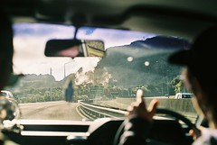 Through the looking glass (Denzel De Ruysscher) Tags: film pentax explore colour 35mm car driving smoke landscape sign window sky green