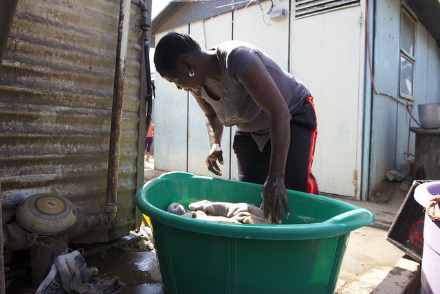 A woman does laundry outside the home Hasan visited in the Township of Alexandra, where shacks have electricity but water and toilets are outside.