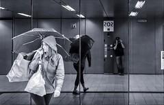 Observation (Heinrich Plum) Tags: heinrichplum plum fuji xe2 xf27mm streetphotography streetphotographie schwarzweiss black white blackwhite observer underobservation beobachtung beobachter spiegelung reflection spiegel mirror munich mnchen subway ubahn bavaria bayern regenschirm umbrella fotograf photographer monochrom monchrome candid