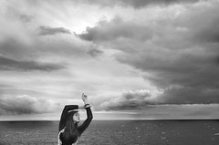 78 /365 'When You're Young, You Run' (Grace_Evangeline) Tags: black white girl arm outstretched clouds sea outdoor nature dress long hair beautiful extreme pretty face light