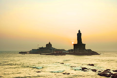 A Beautiful Sunrise On The Southern Tip Of India (Stuck in Customs) Tags: india stuckincustoms treyratcliff southernindia thebayofbengal indianocean arabiansea kanyakumari kerala ocean sea gameofthrones light statue glowing temple dawn sunrise blue purple pink black yellow gold orange green rr dailyphoto horizontal color colour stuckincustomscom 30days2016 hasselblad h5d january 2016 p2016 sunset outdoor tower architecture lighthouse horizon