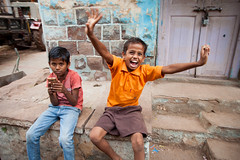 Enthusiastic kid (Scalino) Tags: india karnataka travel trip badami durga temple fromtherickshaw streetphotography street surprise unposed onspot passingby enthusiastic kid playing video game yellow orange yeah smiling surprised