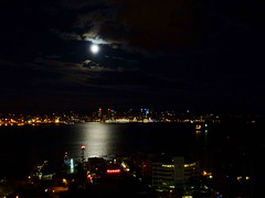 Full moon bathes the Vancouver Harbour in a magical, silvery light (peggyhr) Tags: city blue red sky moon white reflection green yellow skyline clouds silver buildings harbour northshore moonlight southshore lonsdalequay peggyhr colouredights
