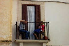 The art of watching being watched (bulgit) Tags: couple watching window curtain balcony light wood sitting chairs free age wisdom calm thinking eyes relaxing village polignanoamare italy outside