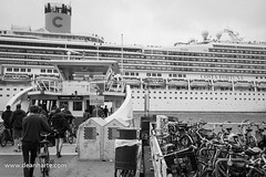 Costa Fortuna and IJveer in Amsterdam (Dean Harte - www.deanharte.com) Tags: costafortuna cruiseship amsterdam bicycle bicycles ijveer ijferry boat vessel nautical sail sailing monochrome filmphotography ilfordfp4 portofamsterdam portscene cruising travel holland thenetherlands nederland nikon f6 black white nikonf6