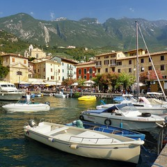 The little harbor of Malcesine between Monte Baldo and lake Garda (Bn) Tags: malcesine harbor harbour picturesque monte baldo lake garda italy italia boat speedboat summer boats sun blue sky church water share cable car veneto fjord mountains holiday cafe restaurants old port vecch
