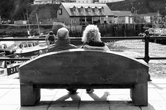 Seat with a view (farwest56) Tags: uk travel england people blackandwhite bw woman holiday man building boats cornwall harbour sony tourists a350