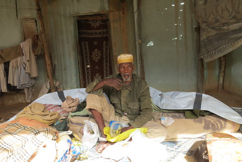 UNHCR News Story: Aid, including tents provided by UNHCR, was distributed to flood victims, such as this old man.