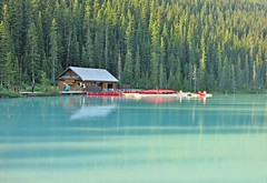 Lake Louise ~ where the boats live - HCS! (karma (Karen)) Tags: trees light canada topf25 docks reflections boats shadows piers lakes pines canoes alberta lakelouise canadianrockies boathouses logcabins banffnp canadanationalparks