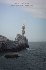 girl on cliff (Ticino-Joana) Tags: ocean sea cliff woman plants nature water floral girl beautiful yellow rock female umbrella vintage outside outdoors person one back rocks pretty alone dress young skirt retro blond parasol single frombehind romantic anonymous caucasian