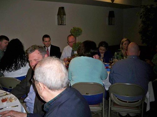 <p>Robert Atkins, founder of Christ's Hands, at a table with guests. (Robert wears the red tie.)</p>
