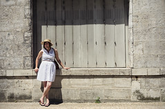 Standing Out (Vemsteroo) Tags: door summer urban woman white france girl lines stone contrast canon town dress adult textures 5d balance walls relaxation juxtaposition provincial individuality mkiii 24105mm