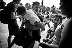 The Training of a Pickpocket (stimpsonjake) Tags: nikoncoolpixa 185mm streetphotography bucharest romania city candid blackandwhite bw monochrome baby child pickpocket woman mother family thief