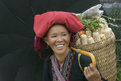 Woman with a basket of corn (tmeallen) Tags: woman smiling blackumbrella basketofcorn vegetables culture reddao daodo ethnicminority traditionalattire redheaddress sapa vietnam borderregions