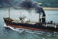 Old Steamer Billowing Smoke, Atami, Japan, 1952 (Wernher Krutein) Tags: travel industry boat ship commerce technology craft vessel cargo business commercial maritime transportation transit hauling nautical traveling fleet shipping merchant schiff freight civilian freighter mariner shipment transporting transshipment freightage