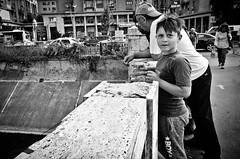 Inner City Fishing with Grandpa (stimpsonjake) Tags: nikoncoolpixa 185mm streetphotography bucharest romania city candid blackandwhite bw monochrome grandpa grandson fishing child look boy