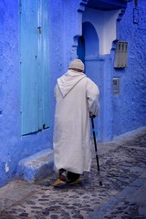 Morning walk (halifaxlight) Tags: morocco chefchaouene medina alleyway man elder walking stick cane robe morning door blue grey street