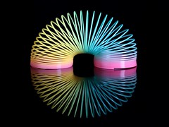 Slinky (Karen_Chappell) Tags: slinky spiral shape abstract stilllife colourful colours multicoloured reflection black pink yellow blue curve product toy
