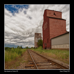 Grain elevators at Creston, British Columbia (kgogrady) Tags: wood old trees summer two canada west color colour building tree grass rock clouds train buildings wooden nikon peeling paint track skies afternoon bc britishcolumbia elevator grain traintracks noone railway stormy nopeople canadian western rails grainelevator creston railwaytracks crestonbc railwayties d700 crestonbritishcolumbia