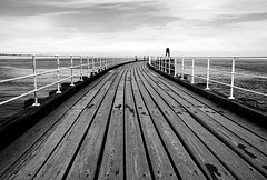 The West Pier (PeteZab) Tags: wood uk england sky blackandwhite bw texture monochrome lines mono pier vanishingpoint boards yorkshire whitby railing 2012 seapeople canoneos50d petezab peterzabulis sigma1770f284dcmacroos