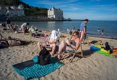 Brits at the seaside. (f22photographie) Tags: seasidescene sunbathing beachscene deckchairs relaxing chillingout readingabook paddlinginthesea llandudno llandudnopromenade llandudnopier northwales britishseasidescene voigtlander15mmf45vmmk1lens
