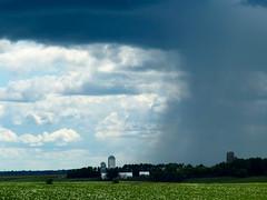 Part clouds and sun, part rain (plethora4834) Tags: windturbine field sky clouds rain weather
