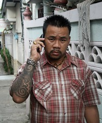 tattoos, bling, and a cellphone (the foreign photographer - ) Tags: portraits silver thailand gold bangkok cellphone jewelry tattoos rings bracelet khlong bangkhen thanon
