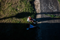 late in the day (ewitsoe) Tags: longshadows shade shadows couple grass fromabove lookingdown bridge shades ewitsoe nikond80 35mm street city life citylife grassy bankofriver summerday polska man andwoman girl boy woman hangingout lunch lateintheday afternoon