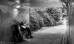 A subway musician. (steve.gombocz) Tags: urbanstreet blacknwhite greyscale streetscene blackwhite whiteblack bwphotos bwstreetscenes bw bwstreet flickrbw bwflickr blackwhitephotos blackwhitephotography flickrstreet blackwhitestreet bwstreetphotography streetlife street streetscenes streetphotographs bwphotographs streetphotography bwphotography streetbw noiretblanc schwartzundweiss negroyblanco zwartwit neroebianco sortoghvid mustavalkoinen svarthvitt svartoghvitt svartochvitt czarnyibiaty pretoebranco noirblanc schwartzweiss negroblanco nerobianco pretobranco olympus olympususers olympuscamerausers photosinblackandwhite flickrblackandwhitephotos olympuseurope olympusbw olympusmzuiko25mmf18lens olympusm25mmf18 olympusem5mark2 olympusdigitalcamerausers micro43rdsuk olympuszuikodigitalclub olympusstreet streetmusic streetentertainment subway streetmuscian explorebw flickraddict flickraddicts explorestreet keswick blackandwhitephotographs subwaymusic