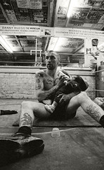 Boxer Feeding Baby (www.andrewlever.com) Tags: lighting family people blackandwhite baby man male love monochrome sport kids portraits children person one droplets holding fighter moody child adult emotion feeding unity father documentary dramatic son tattoos story boxer bond strong strength caring boxing care athlete drama sporting powerful gentle skinhead reportage tattooed